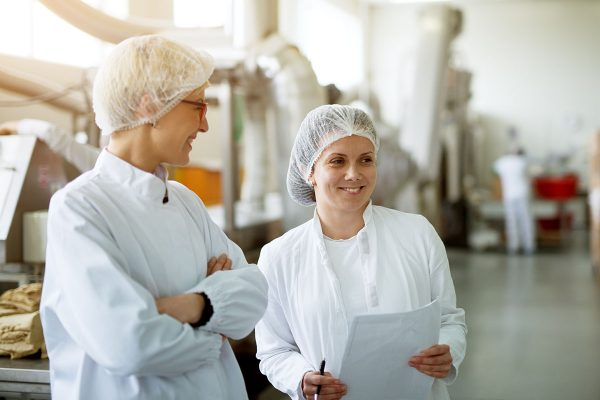 Two young gorgeous female workers are having a chat while one of them holds papers with statistics.