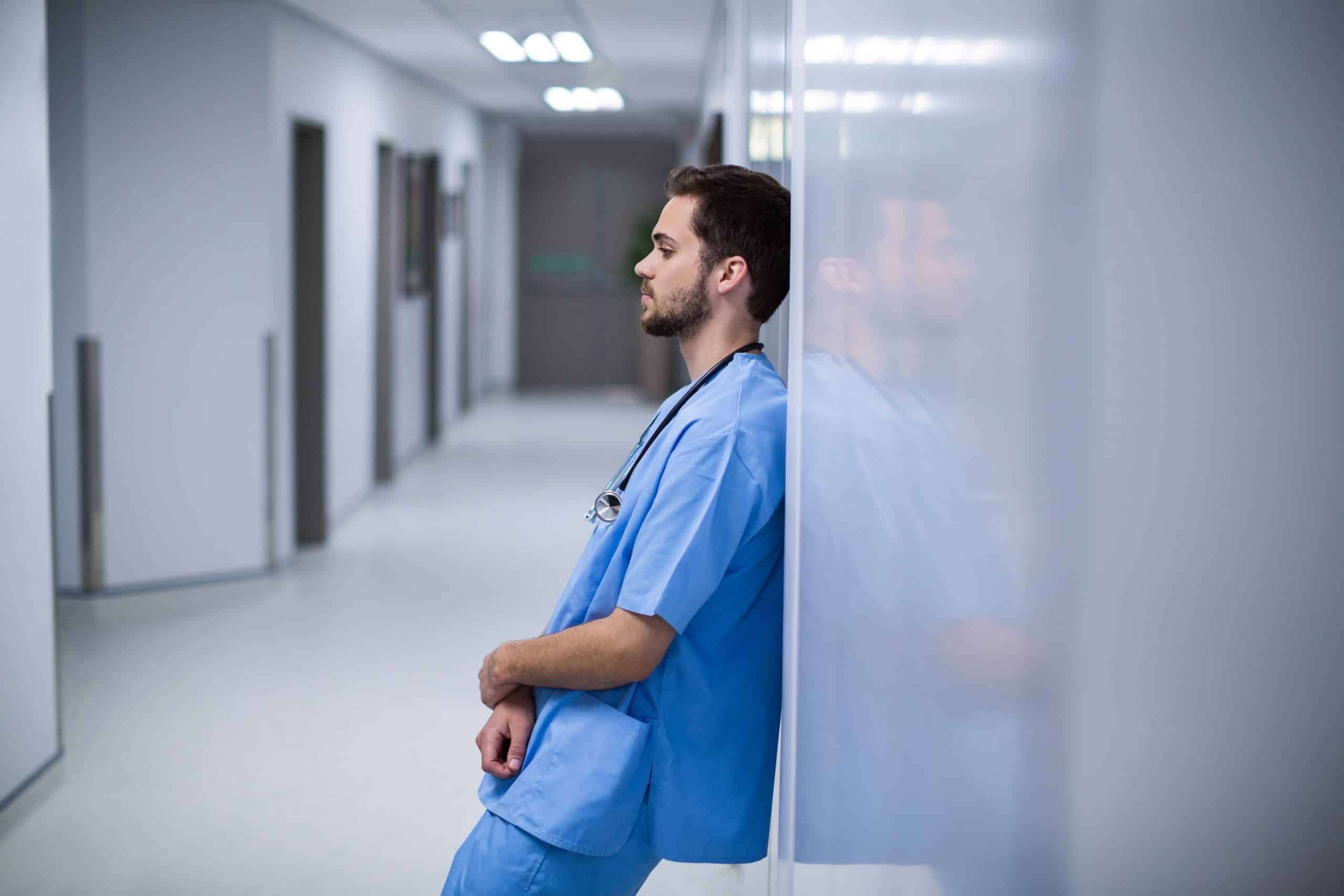 Tensed male nurse leaning on wall in corridor